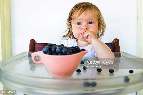 Caucasian baby girl eating blueberries