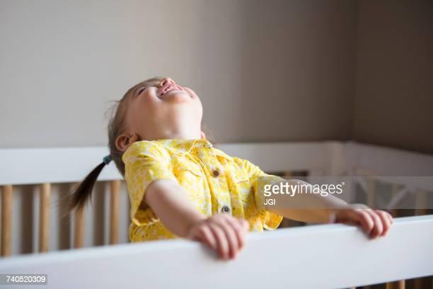Caucasian baby girl laughing in crib