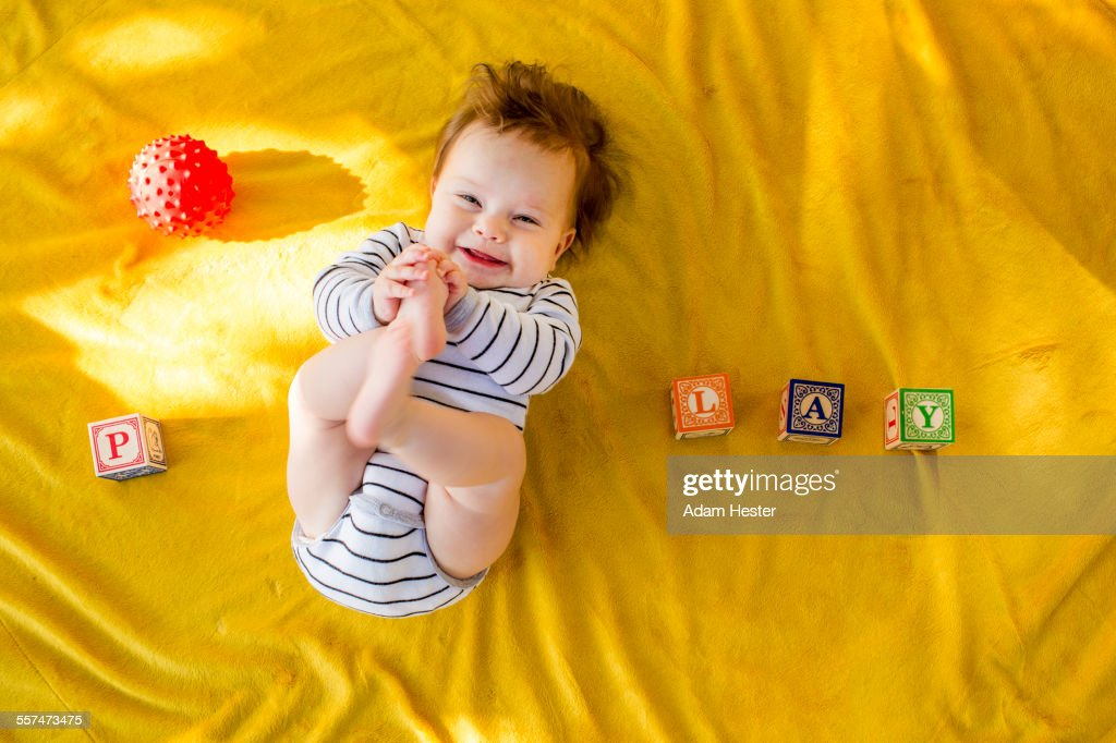 Caucasian baby girl playing with blocks on bed : Stock Photo