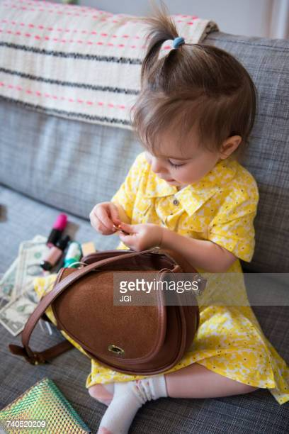 Caucasian baby girl playing with purse on sofa