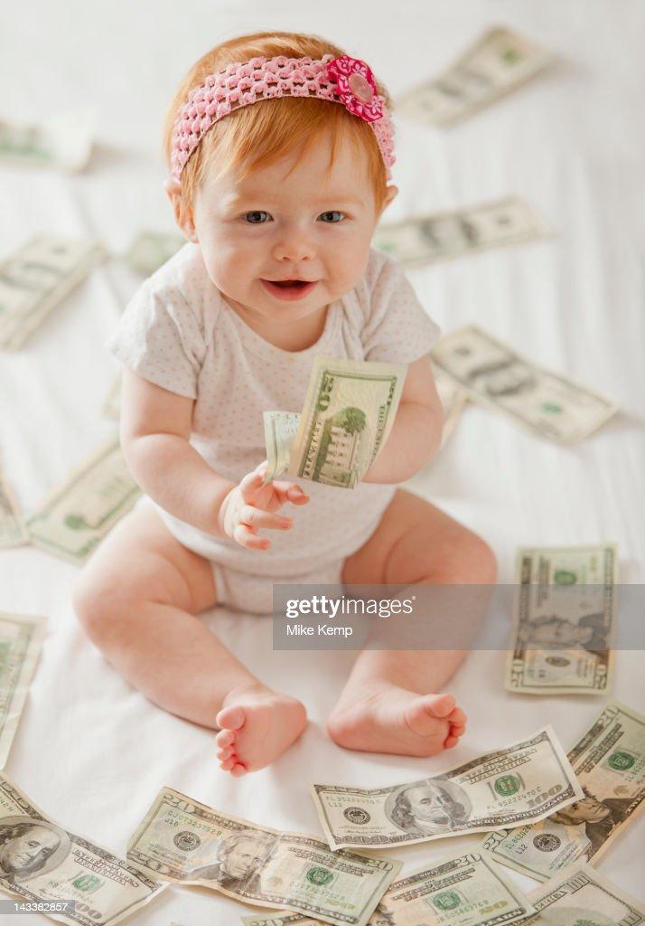Caucasian baby girl playing with twenty dollar bills : ストックフォト