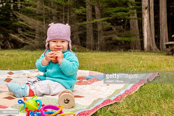 Caucasian baby girl sitting on blanket in grass