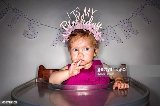 Caucasian baby girl wearing birthday crown