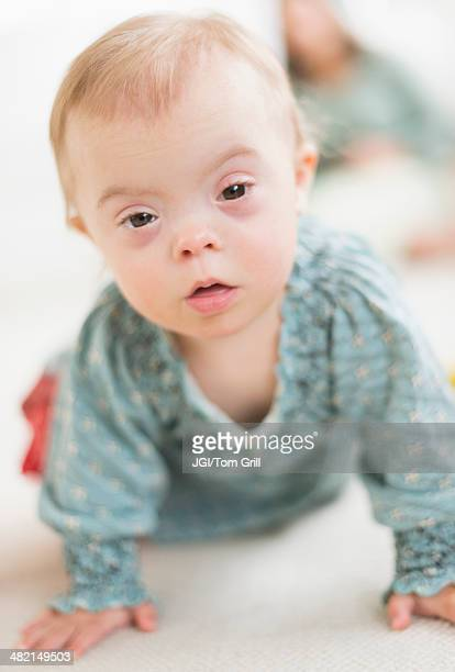 Caucasian baby girl with Down Syndrome crawling