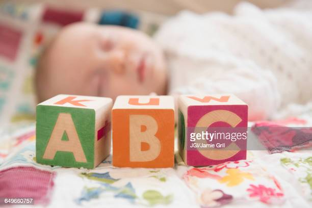 Caucasian baby napping near wooden blocks