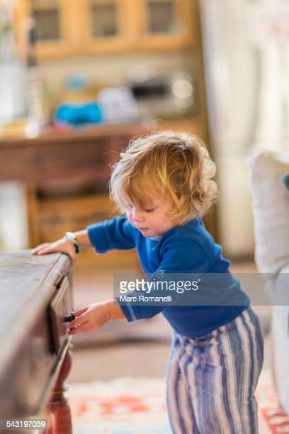 Caucasian baby opening coffee table drawers