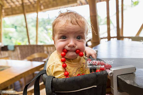 Caucasian baby playing with beads in high chair