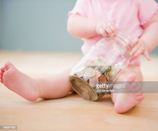 Caucasian baby playing with jar of coins