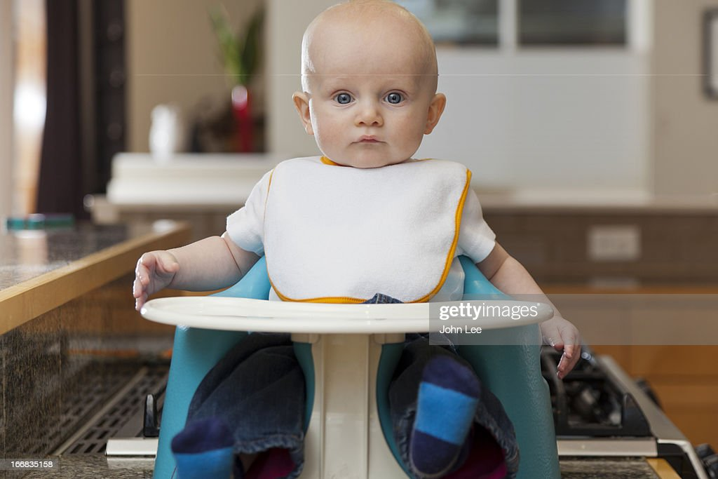 Caucasian baby sitting in high chair : Stock Photo