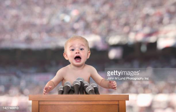 Caucasian baby speaking at podium