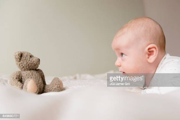 Caucasian baby staring at teddy bear on bed