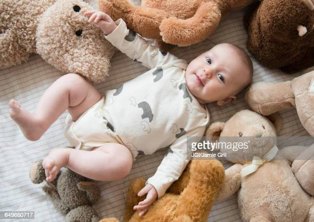 Caucasian baby stuffed animals on bed