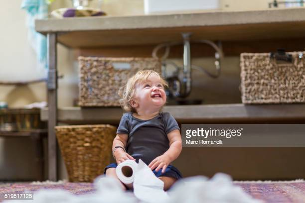 caucasian baby unraveling toilet paper in bathroom - funny toilet paper stock pictures, royalty-free photos & images