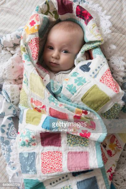 Caucasian baby wrapped in blanket
