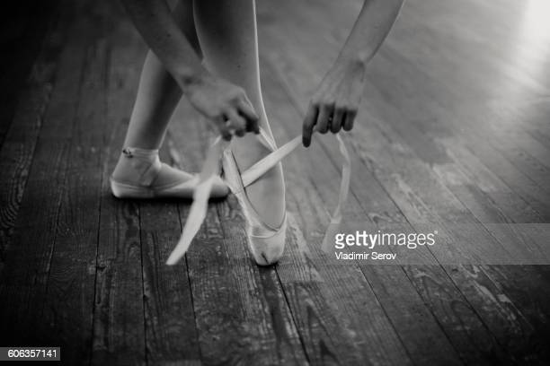 Caucasian ballerina tying pointe shoes