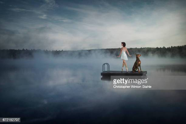 Caucasian ballet dancer on floating dock in foggy lake with dog