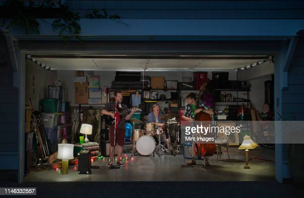 caucasian band playing in garage - performance group stock pictures, royalty-free photos & images