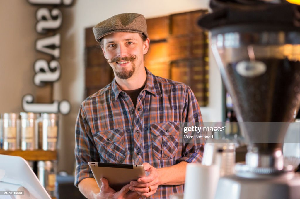 Caucasian barista holding digital tablet in cafe : Stock Photo