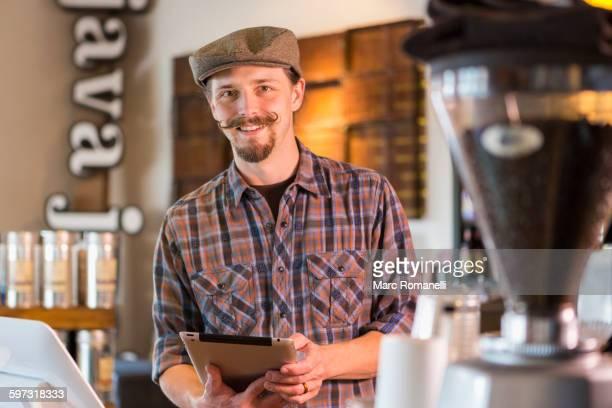 Caucasian barista holding digital tablet in cafe