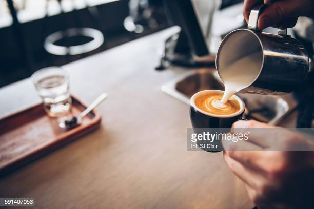 caucasian barista pouring coffee drink in cafe - espresso stock photos and pictures