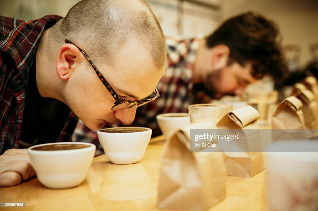 Caucasian baristas smelling coffee in cups : Stock Photo