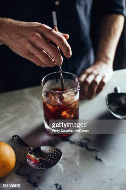 Caucasian bartender mixing cocktail in glass