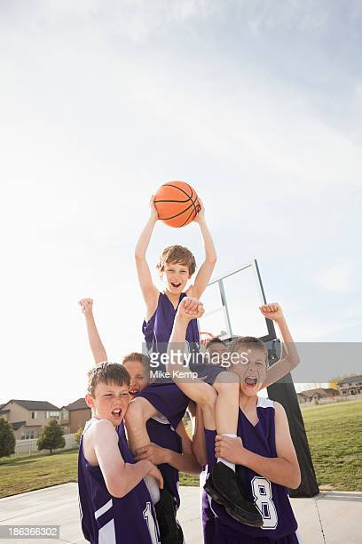 caucasian basketball team cheering on court - basketball team stock pictures, royalty-free photos & images