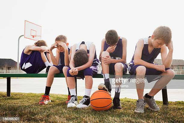caucasian basketball team sulking by court - nederlaag stockfoto's en -beelden