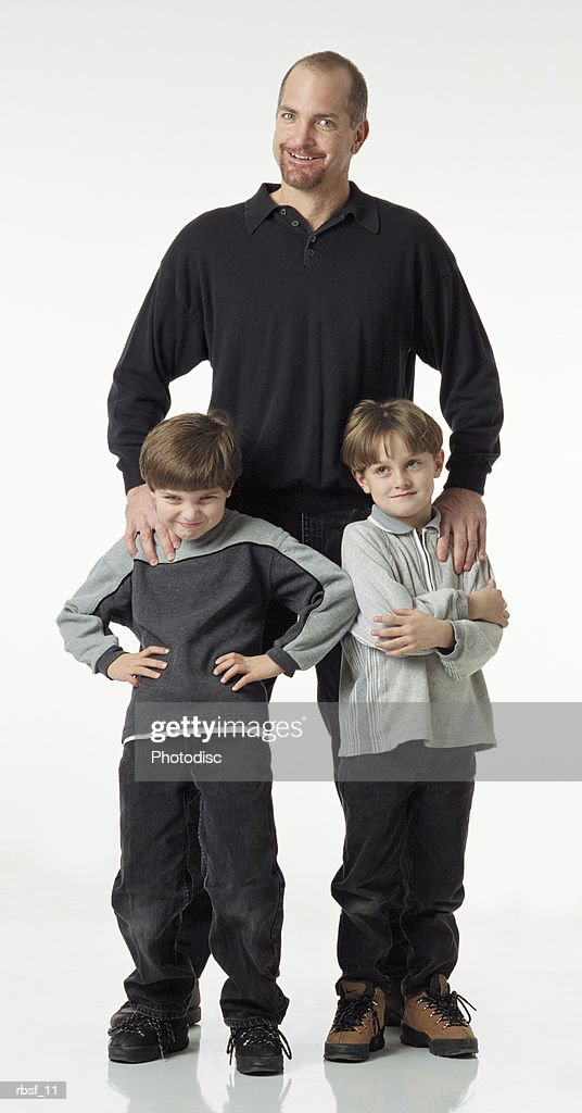 caucasian bearded dad stands and smiles behind two young boys who give attitude dressed in greasy and blacks : Foto de stock
