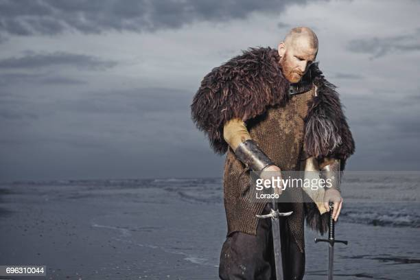 caucasian bearded viking man in the sea at dusk - historical clothing stock pictures, royalty-free photos & images