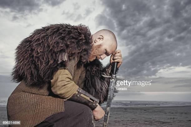 夕暮れ時に海で白人のひげを生やしたバイキング男