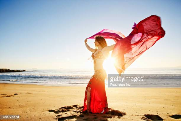 caucasian belly dancer holding scarf on beach - belly dancing stock photos and pictures