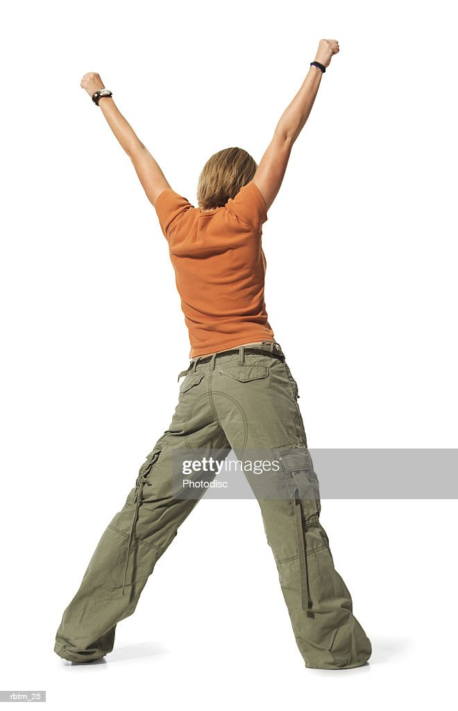 caucasian blonde female teen in green pants and orange shirt stands backwards with arms in the air : Foto de stock