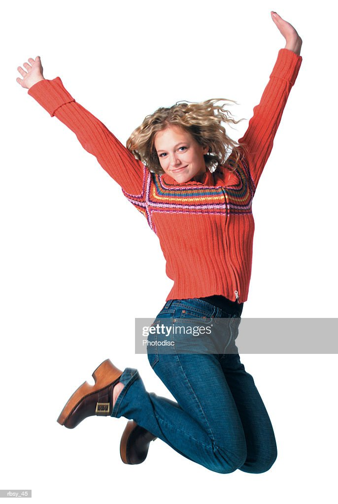 caucasian blonde female teen in jeans and red sweater jumps up into the air and throws her arms up : Foto de stock