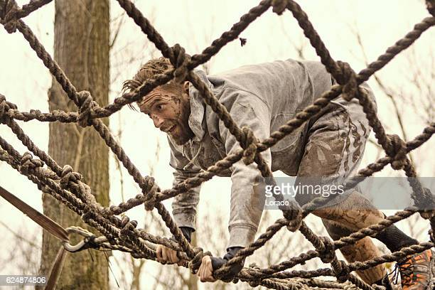 caucasian blonde handsome man climbing obstacle during a mud run - obstacle course stock pictures, royalty-free photos & images