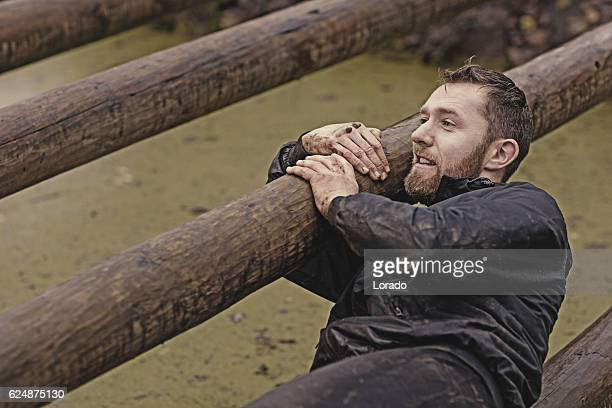Caucasian blonde handsome man crawling under obstacle during mud run