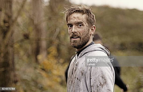 caucasian blonde handsome man posing during a mud run - macho stock pictures, royalty-free photos & images