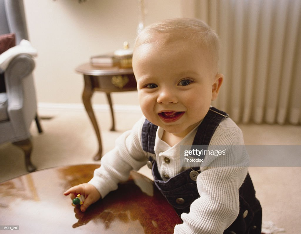 A caucasian blonde male toddler leans against a table and grins : Stockfoto