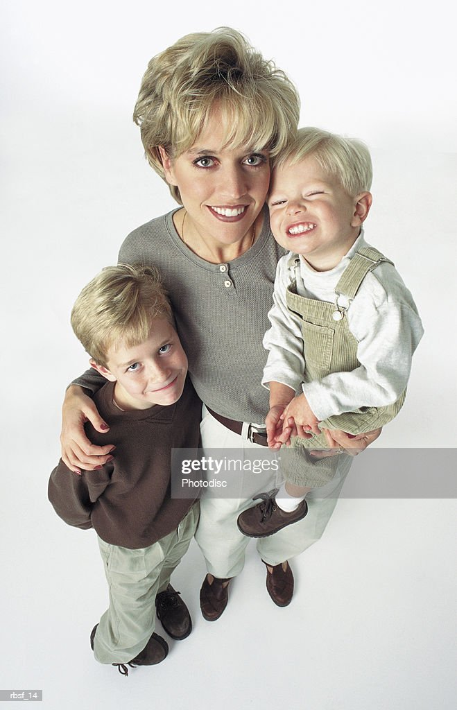 caucasian blonde single mother standing with two young happy children all dressed in khaki : Foto de stock