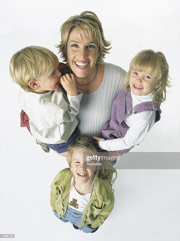 caucasian blonde woman laughs holding two kids and with one standing in front of her : Foto de stock