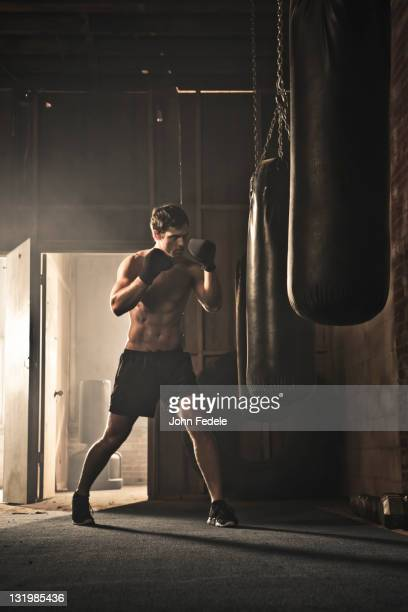 Caucasian boxer hitting punching bag