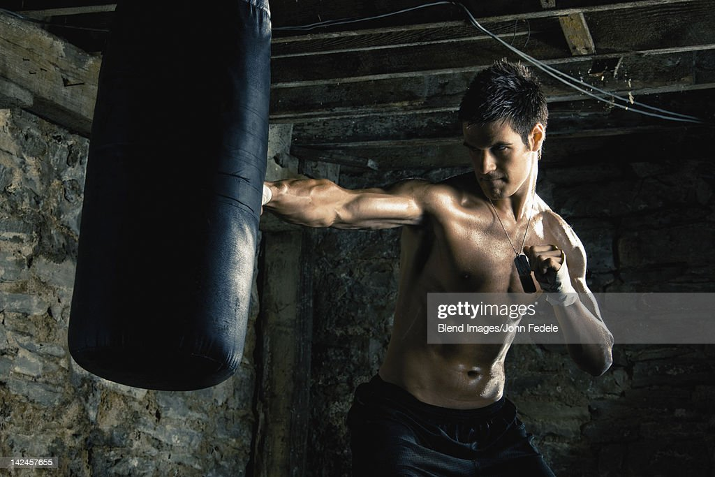 Caucasian boxer training and hitting punching bag : Stock Photo