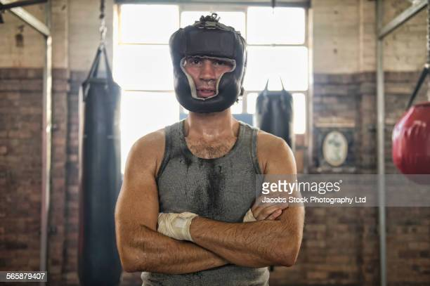 Caucasian boxer wearing protective headgear in gymnasium