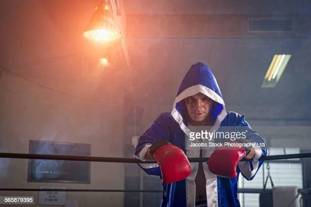 Caucasian boxer wearing robe in boxing ring