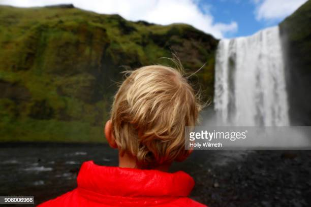 Caucasian boy admiring scenic view of waterfall