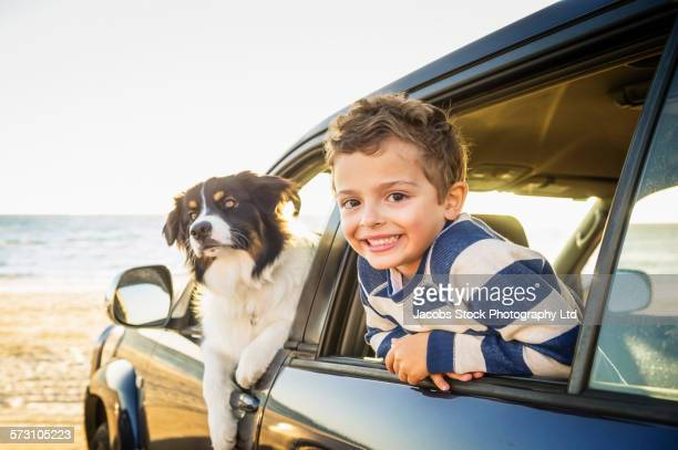 Caucasian boy and dog in car windows on beach
