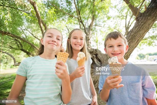 Caucasian boy and girls eating ice cream cones