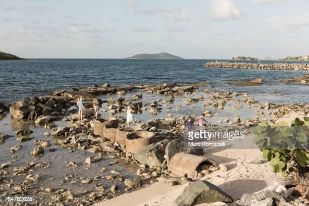 Caucasian boy and girls walking on rocks at beach