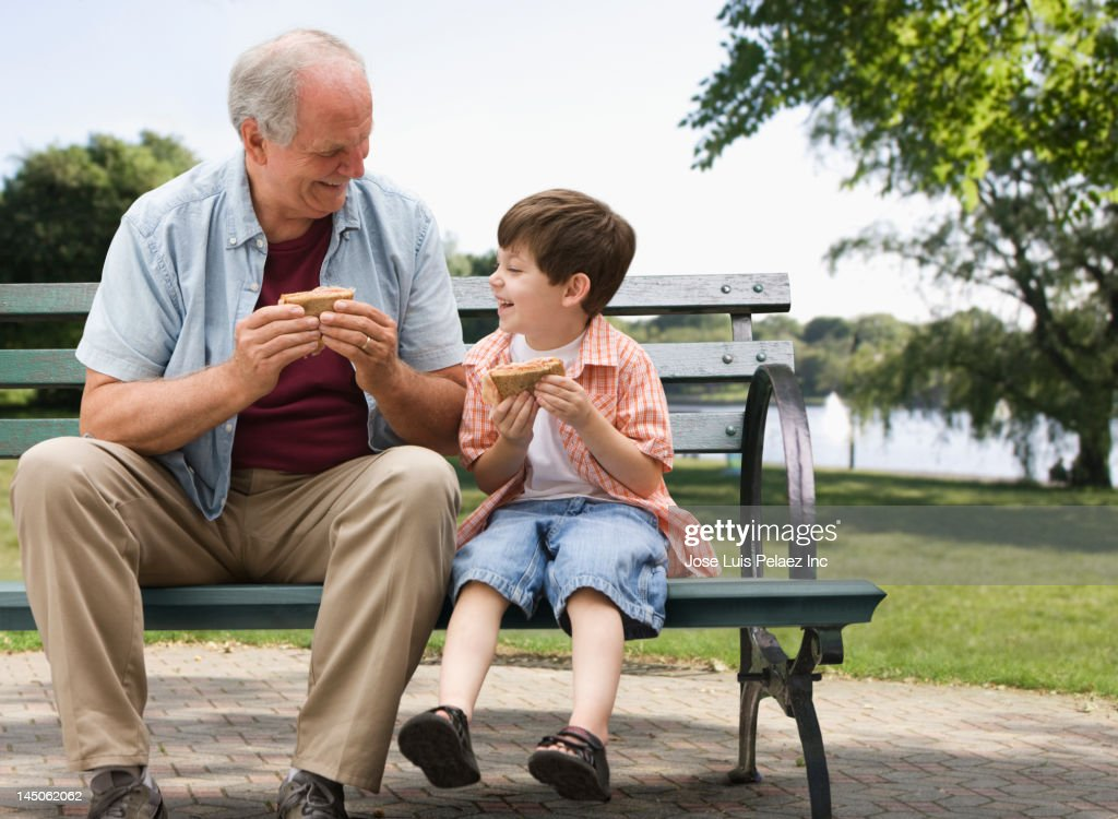 Caucasian boy and grandfather eating in park : Stock Photo
