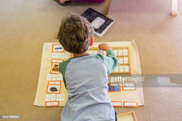 caucasian boy arranging cards in classroom - montessori education stock pictures, royalty-free photos & images